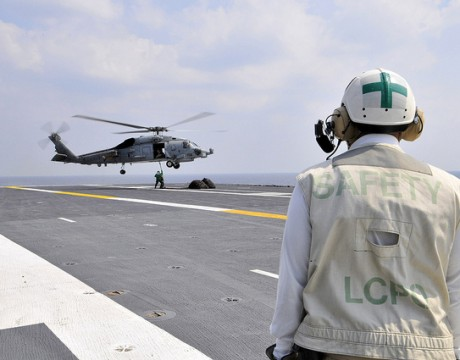 Chief Aviation Boatswain's Mate (Handling) Otis McKinney monitors logistics specialists from supply department aboard the aircraft carrier USS George Washington (CVN 73), as they secure a pole pendant to an MH-60R helicopter, assigned to the Scorpions of Helicopter Anti-Submarine Squadron Light (HSL) 49 on the flight deck during a vertical replenishment with USNS Pecos (T-AO 197).  (U.S. Navy Photo by Mass Communication Specialist 3rd Class Marcos Vazquez)