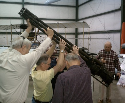 Directed by Dave Seeman, right, a group of Patuxent River Naval Air Museum volunteers shift an aircraft gatling gun to make space for a new display.