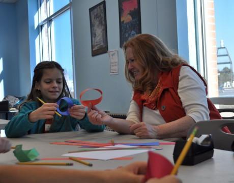 Karen Garner, President of RED-INC., creates a Möbius strip with students at SoMD Math Circle.
